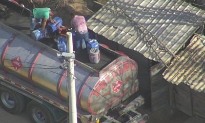 Momentos  en los que varias personas extraen la gasolina remanente de los carrotanques que transportan el combustible hacia el departamento de La Guajira.