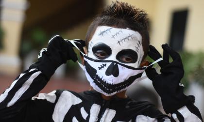 Una sonrisa dibujada en el tapabocas complementa el disfraz de la muerte.