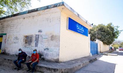 Dos hombres conversan a las afueras de las instalaciones de la empresa Triple A en el barrio Primero de Mayo, en el municipio de Soledad.