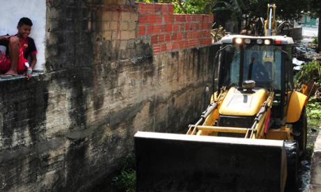 Un menor observa la remoción de sedimentos realizada ayer en un tramo del arroyo por operarios de A Construir S.A.