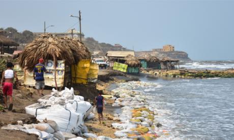 Un niño camina entre hileras de sacos, puestos para mitigar el impacto del mar.