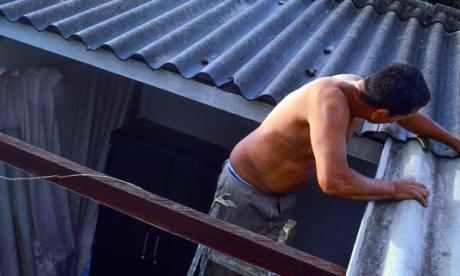 Hombre afectado por el vendaval arregla una de las tejas de su hogar.