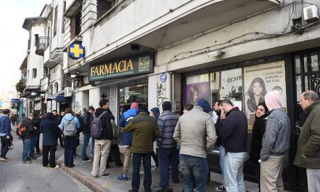 Numerosas personas hacen fila en una farmacia en Montevideo para comprar marihuana con fines recreactivos.