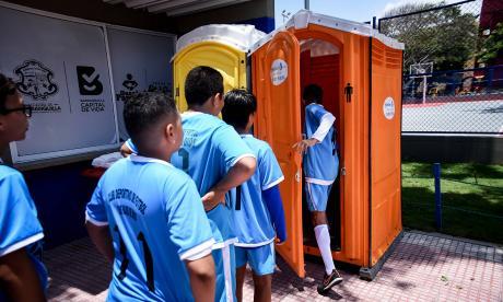 Niños que jugaron fútbol en la cancha del parque Los Andes ingresan al baño.