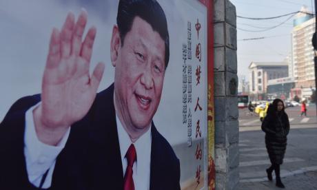 Una mujer pasa frente a un cartel del presidente chino Xi Jinping, en Pekín.