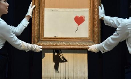 Banksy destruyó la obra 'Love is in the bin' para denunciar la mercantilización.