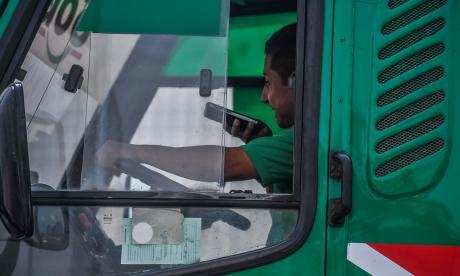 Un conductor de vehículo de transporte público habla por celular mientras conduce.