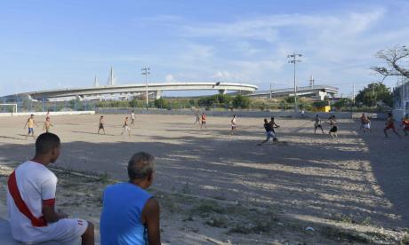 Una decena de niños juega fútbol sobre la arena de la cancha de La Chinita mientras dos personas observan el puente Pumarejo.