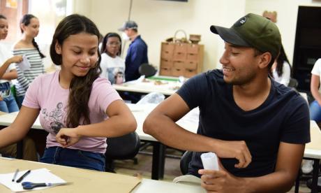 Dos estudiantes de Unimagdalena se saludan de codos, como recomienda la OMS.
