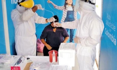Dos trabajadores de la salud toman la muestra a un paciente para determinar si está contagiado