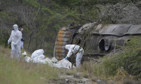Técnicos forenses inspeccionaron los cadáveres calcinados que quedaron cerca al camión que estalló