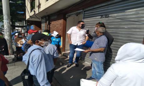 Usuarios hacen fila para recibir los medicamentos en una droguería.