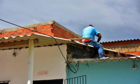 Vecinos de un sector de La Playa repara el techo dañado por las fuertes brisas registradas en los últimos días antes de las lluvias.