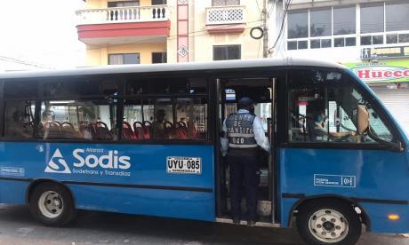 Un agente de tránsito inspecciona el aforo en un bus de transporte público.
