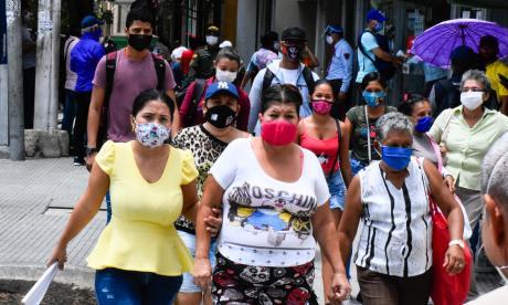 Un grupo de personas utilizando tapabocas mientras camina por las calles.