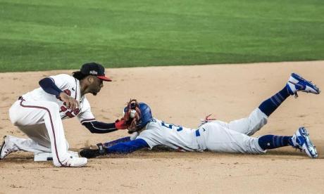 Mookie Betts, de los Dodgers, se barre en la almohadilla intermedia ante la defensiva del segunda base de Bravos, Ozzie Albies.