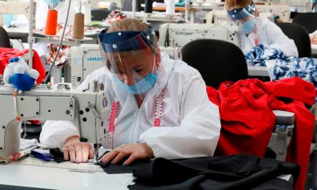 Varias trabajadoras de una empresa del sector de confecciones usando elementos de bioseguridad.