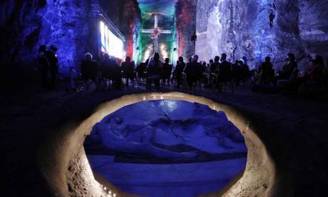 Visitantes observan una proyección en las rocas salinas de los socavones de la Catedral de Sal de Zipaquirá