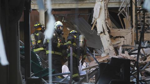 Bomberos revisan el lugar tras la conflagración.