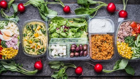 Diversos alimentos saludables empacados en portacomidas hechos en material plástico.