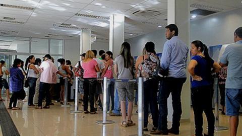 Personas haciendo filas para realizar un trámite.