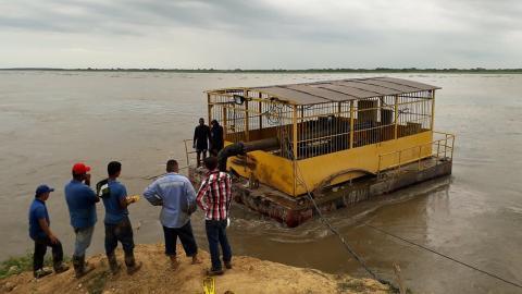 Trabajadores mueven la barcaza en jurisdicción de Campo de la Cruz.