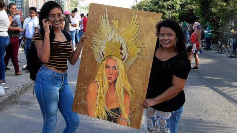 Dos fanes de Shakira muestran un cuadro para homenajear a la cantante barranquillera.