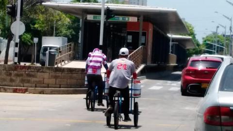 Dos vendedores ambulantes transitan por el carril de Transmetro en la carrera 46.