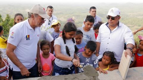Una niña coloca la primera piedra en el mirador.