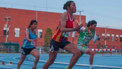 Martha Hernández corriendo la prueba de 100 m.