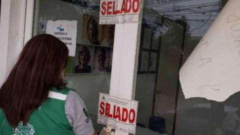 Funcionaria de la Secretaría de Salud pone el sello en la puerta de la IPS Esimed.