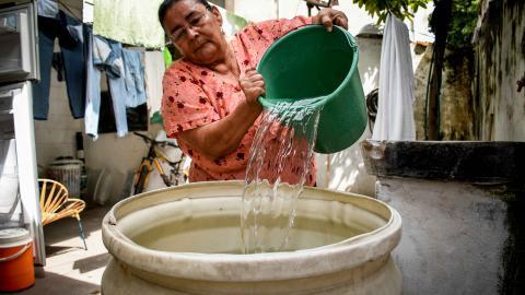 Magaly Velásquez, habitante del barrio Montecristo, vierte agua en un tanque para almacenarla.