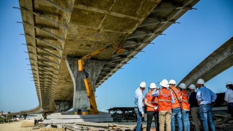 """El grupo de expertos observa a los obreros que reparan las """"fisuras"""" en el tablero del Puente Pumarejo."""