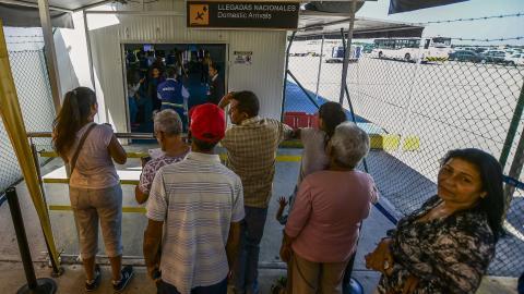 Personas esperan a que un grupo de pasajeros salga de la sala de llegadas en el aeropuerto Ernesto Cortissoz.