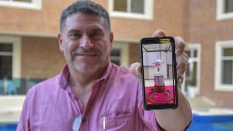 Luis Fernando Suárez muestra en su celular la réplica de la Copa Libertadores que le compró a los jugadores.