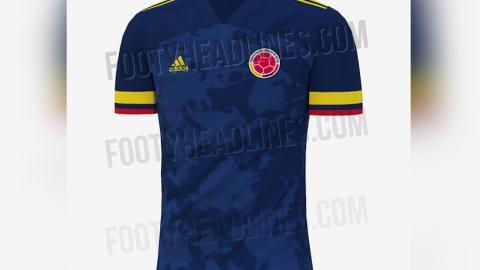 La camisa es azul oscura con la bandera de Colombia en las mangas.