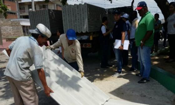 Dos damnificados reciben varias láminas para reponer el techo dañado por el vendaval.