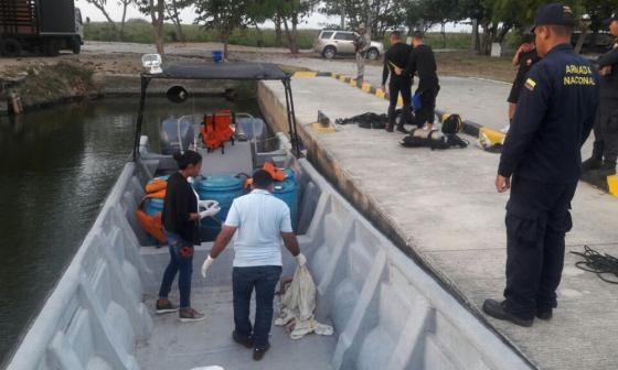 Peritos forense de la Sijín practican el levantamiento del cadáver, ante la mirada de varios uniformados de la estación de Guardacostas.