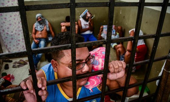 José Rivera se apoya a la reja de la carceleta ya que su enfermedad no le permite mantenerse en pie sin ayuda.
