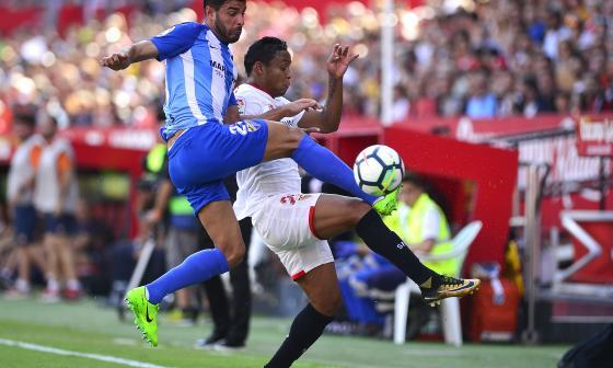 Luis Fernando Muriel lucha una pelota con el defensa del Málaga, Miguel Torres.