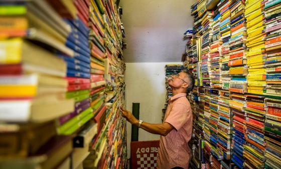 Jaime Barcinilla, uno de los 78 libreros que tiene el Centro Cultural del Libro, mira de arriba hacia abajo  los miles de ejemplares que tiene.