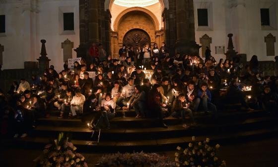 Amigos de los periodistas asesinados encienden velas frente a la Catedral Metropolitana de Quito.