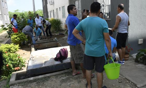 Residentes extraen agua de un tanque comunal.