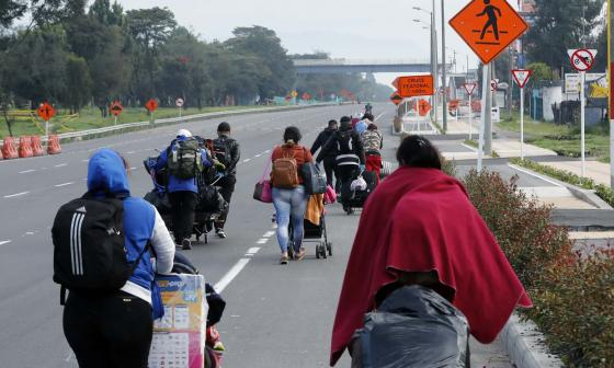 Varios venezolanos se desplazan por una carretera.