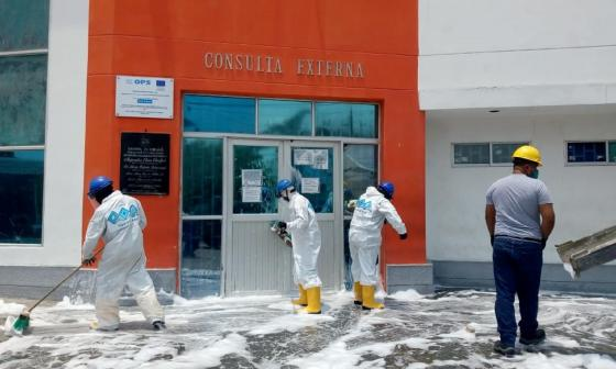 Operarios adelantan las labores de limpieza en las afueras de un puesto de salud.