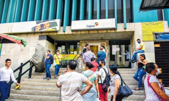 Personas hacen fila para sacar dinero en un cajero