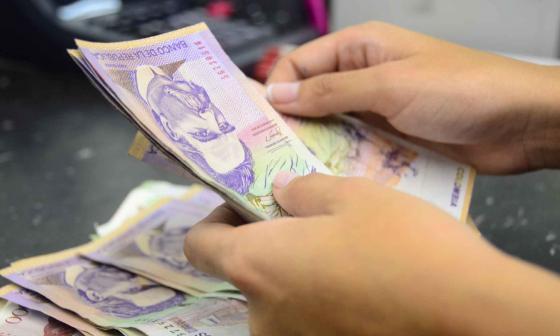 Una persona cuenta billetes de varias denominaciones.