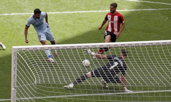 El delantero del Atlético de Madrid, Diego Costa, dispara ante el portero del Ahtelic, Unai Simón, para marcar el gol del empate.