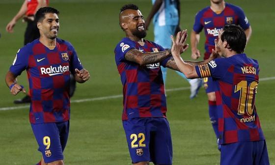 Messi celebra su gol de penal con Arturo Vidal. Luis Suárez llega para unirse a la celebración.