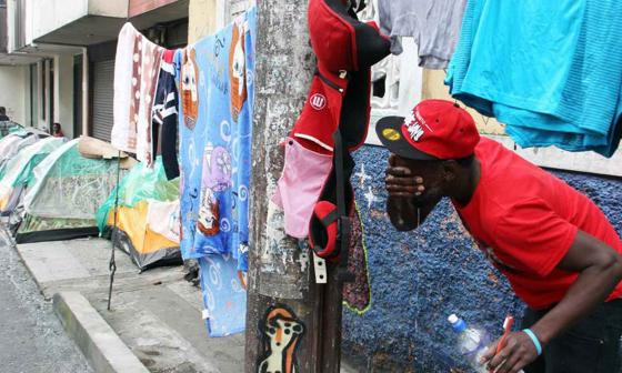 Un migrante haitiano se lava la cara.